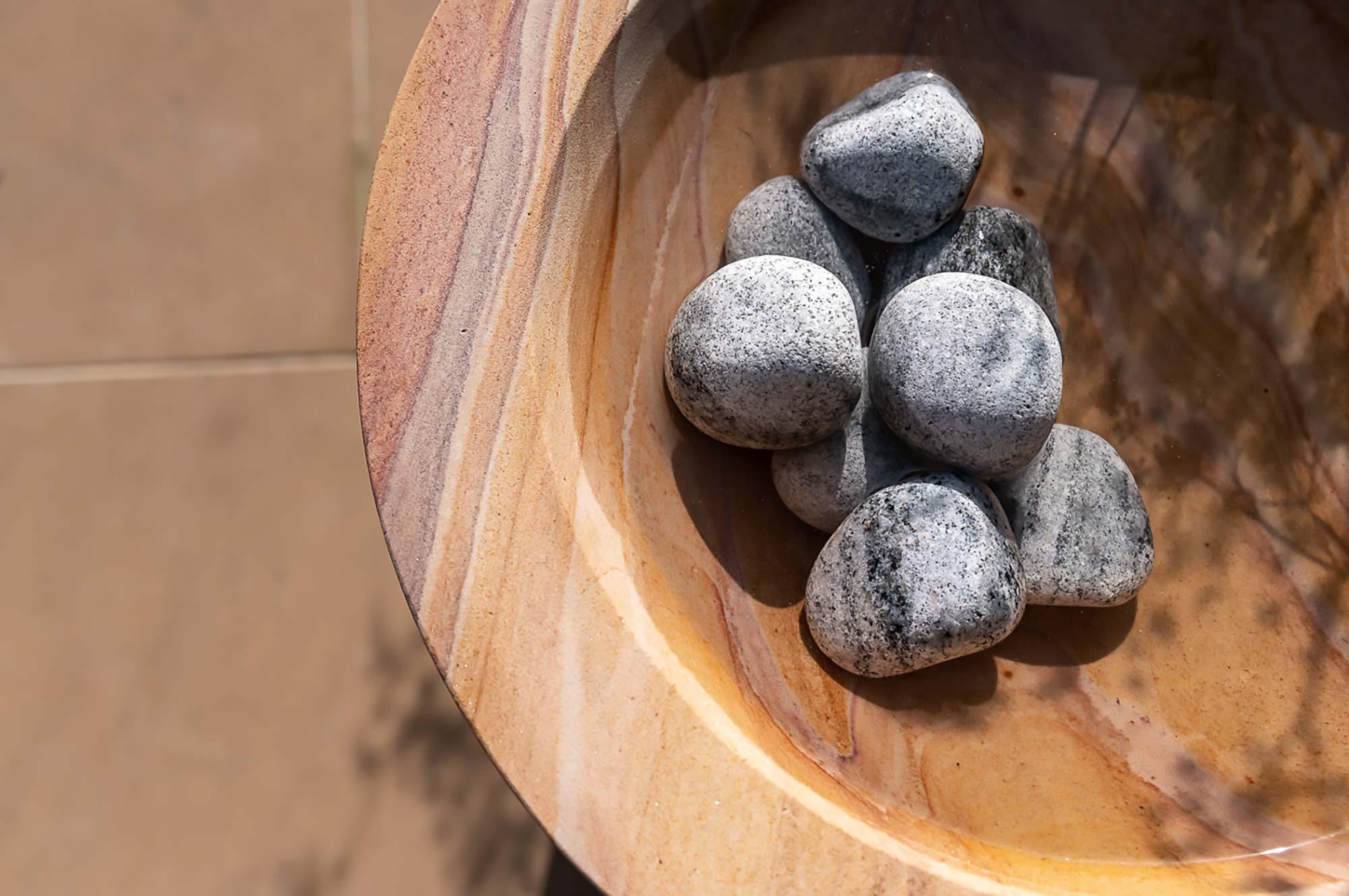 pebbles in sandstone bowl